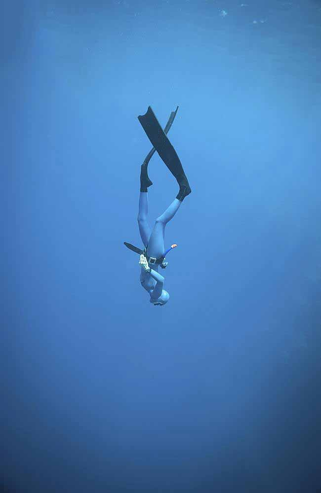 A woman freediving in the ocean.