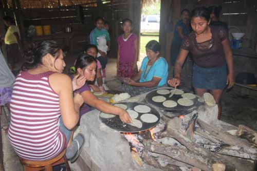 """The tortillas are are cooked on  top of the iron """"comal"""" above the fire fed with wood"""