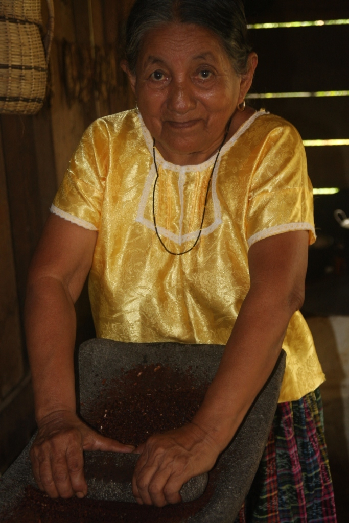 Grinding cocoa for a drink on an old grinding stone made from volcanic lava