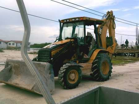 Is this a Bobcat or Backhoe?  How much would it weigh with a load of cement blocks on the front?