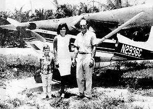 Johnny Greif III with parents Celi McKorkle and John Greif Sr. in front of the first plane to touchdown on Ambergris Caye.